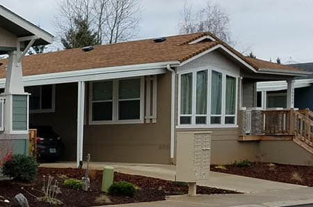 Manufactured home with carport, patio, and a big bay window located in in a manufactured home community.