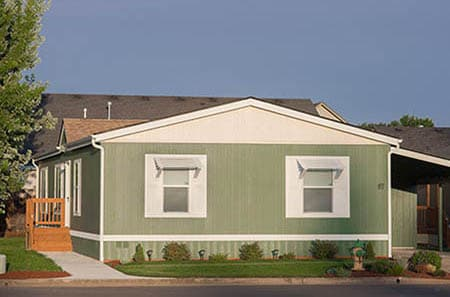 Double-Wide green manufactured home with carport and staircase.